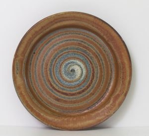 Large platter in rustic brown with a spiral decoration in rutile.